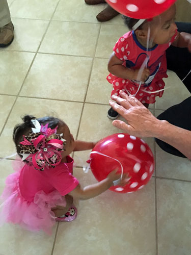 Trying to bounce her balloon like a ball with the help of a friend.